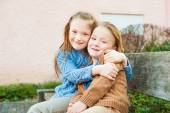 Two cute kids sitting on a bench, big sister hugging little brother — Stock Photo