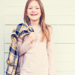 Fashion portrait of a cute little girl of 7 years old, wearing pink shirt, holding yellow and blue plaid cardigan, toned image — Stock Photo #69867231