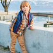 Outdoor portrait of a cute fashion little boy of 4 years old, wearing blue waistcoat, plaid shirt, beige trousers and sneakers — Stock Photo #69867297