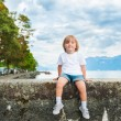 Adorable little boy resting by the lake on a nice summer evening, wearing white shirt, shorts and grey sneakers — Photo #69868197