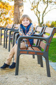 Funny little boy resting on a bench in the park, wearing blue waistcoat and shoes — Stock Photo