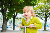 Adorable toddler boy having fun on playground, wearing bright green pullover — Stock Photo