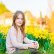Adorable little girl playing with flowers in the park at sunset — Stock Photo #70019409