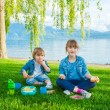 Two cute kids, little girl and her brother, having a picnic outdoors by the lake — Stock Photo #70531955