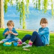 Two cute kids, little girl and her brother, having a picnic outdoors by the lake — Stock Photo #70531959