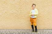 Fashion portrait of a cute little girl of 7 years old, wearing blouse, yellow jacket, orange skirt and black rain boots — 图库照片