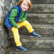 Outdoor portrait of a cute little blond boy wearing colorful clothes, yellow jeans, green pullover, blue waistcoat and boots, standing on stairs in a city — Stock Photo #71819527
