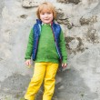 Outdoor portrait of a cute little blond boy wearing colorful clothes, yellow jeans, green pullover, blue waistcoat and boots, standing next to stone wall in a city — Stock Photo #71819643