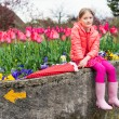 Outdoor portrait of a cute little girl, sitting next to flowerbed full of tulips, wearing bright pink clothes and rain boots, holding umbrella — Stock Photo #71819973