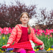 Outdoor portrait of a cute little girl of 7 years old, wearing bright pink jacket, holding umbrella — Stock Photo #71820225