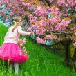 Sweet little girl posing next to a japanese cherry tree in full blossom, wearing bright pink tutu skirt, back view — Stock Photo #71820745