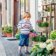 Outdoor portrait of a cute little boy, playing with flowers in front of a flower shop — Stock Photo #71820945