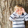 Little 4 year old blond caucasian boy in front of an old and massive tree pretending to take a picture with his hands. — Stock Photo #71821139