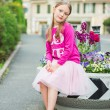 Fashion portrait of a cute little girl of 7 years old, wearing bright pink top, tutu skirt and ballerina shoes — Stock Photo #71821515