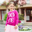 Outdoor portrait of a pretty little girl, wearing bright pink top and tutu skirt — Stock Photo #71821541