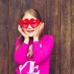 Funny portrait of a cute little girl wearing big heart shaped sunglasses — Stock Photo #71821877