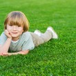Outdoor portrait of adorable little blond boy laying on a bright fresh green lawn — Stock Photo #71822005