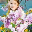 Spring portrait of a cute little girl playing at sunset with flowers of japanese cherry in blossom — Stock Photo #71822089
