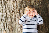 Little 4 year old blond caucasian boy in front of an old and massive tree pretending to take a picture with his hands. — Stock Photo