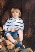 Cute little blond boy sitting on cut wood and leaning on an old wooden wall, wearing white pullover, denim shorts and blue moccasins — Stock Photo