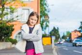 Outdoor portrait of a cute little girl in a city, wearing warm grey knitted jacket, standing next to the road — Stockfoto