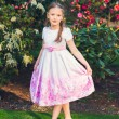 Outdoor vertical portrait of a cute little girl, wearing beautiful bridesmaid dress, toned image — Stock Photo #72631975