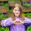 Outdoor portrait of a cute little girl under the rain, wearing purple rain coat, making heart sign with her hands — Stock Photo #72632643