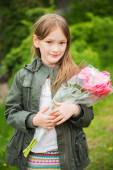 Outdoor portrait of a cute little girl, wearing khaki parka, holding bouquet of pink peonies — Stock Photo