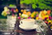 Empty cup of coffee with traces of lipstick on the table under the rain, outdoors, toned image — Stock Photo