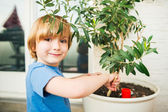 Cute little boy playing with garden tools on the balcony — Stock Photo