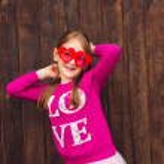 Funny portrait of a cute little girl wearing big heart shaped sunglasses — Stock Photo #74114749
