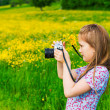Cute little girl taking pictures of the nature, holding a camera and bouquet of yellow buttercups — Stock Photo #74117961