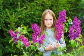 Outdoor portrait of a cute little girl against beautiful lilac on a nice spring day — Stock Photo