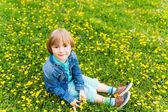 Cute little boy resting outdoors, sitting on a lawn, wearing denim shirt — Stock Photo