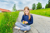 Cute little girl of 7 years old resting in a countryside, playing with flowers on a farmland — Stock Photo