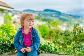 Outdoor portrait of a cute little boy with the beautiful view behind, wearing denim shirt and pink top — Stock Photo
