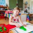 Cute little girl working in a classroom — Stock Photo #75733463