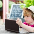 Cute little boy playing with tablet pc in a cafe — Stock Photo #75734293