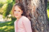 Outdoor portrait of a cute little girl of 7 years old, resting in a park, leaning on a tree — Stock Photo