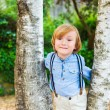 Close up portrait of adorable little blond boy, wearing pants with suspenders — Stock Photo #75741555