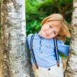 Close up portrait of adorable little blond boy, wearing pants with suspenders — Stock Photo #75741859