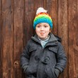 Outdoor portrait of a cute little boy wearing grey coat and colorful hat, standing against wooden door — Stock Photo #76951697