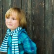 Fashion portrait of a cute little blond  boy against wooden background, wearing emerald shirt and scarf — Stockfoto #76953375