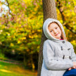 Autumn portrait of a cute little girl playing on a tree in a beautiful park on a nice sunny day — Stock Photo #78488044