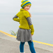 Cute little girl having fun outdoors on a cold day, dancing next to beautiful lake, wearing green woolen pullover, hat and warm boots — Stock Photo #78488658