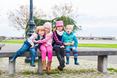 4 cute kids sitting in the bench in a city, wearing warm waistcoats and boots — Stock Photo