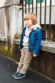 Fashion portrait of adorable little boy wearing denim jacket, beige corduroy trousers, gray sweatshirt and blue shoes — Stock Photo