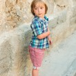 Fashion little boy wearing blue plaid shirt and red printed shorts — Stock Photo #81150872