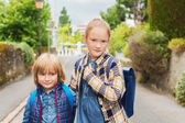 Cute kids with backpacks walking to school — Stock Photo