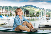 Fashion portrait of a cute little blond boy sitting on a bench by the lake, wearing denim shirt and beige trousers — Stock Photo